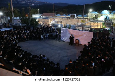 """MERON, ISRAEL - MAY 6, 2018: The grand Rabbi of the """"Seret-Vizniz"""" hasidic sect in Meron, Israel with his followers after the Jewish holiday of """"Lag Baomer"""""""