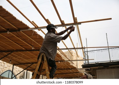 "MERON, ISRAEL - SEPT 13, 2018: Unidentified Jewish men build a huge temporary hut called ""sukkah"" for the holiday of Sukkot, by the grave of Rabbi Shimon Bar Yochai in Meron, Israel"
