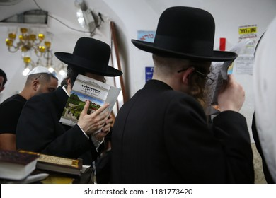 """MERON, ISRAEL - SEPT 9, 2018: Unidentified ultra orthodox Jewish man prays the psalms prayer called """"tikkun haklali"""" with his head covered by the prayer book, in Meron, Israel"""