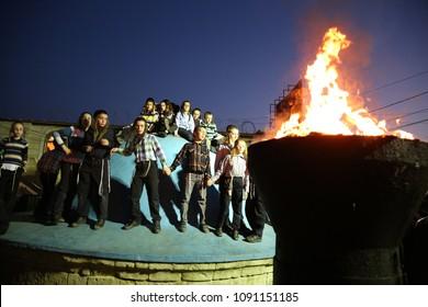 MERON, ISRAEL-APR 29, 2018: Unidentified orthodox Jewish men. boys gather around bonfire on the dome/ roof of the tomb of Rabbi Shimon Bar Yochai on the Jewish holiday of Lag Baomer in Meron, Israel
