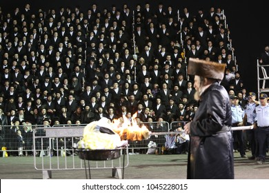 MERON, ISRAEL-MAY 14, 2017: Crowd of unidentified Hasidic Jews watch their Rabbi, the Rabbi of Rachmastrivka, light bonfire in honor of Rabbi Shimon Bar Yochai in Meron, Israel on Lag Baomer holiday