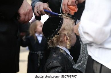 MERON,ISRAEL- MAY 26, 2016: An unidentified Hasidic Rabbi gives first haircut to an unidentified Jewish Hasidic boy with blond curls as is tradition upon the grave of Rabbi Shimon on Lag Ba'omer.