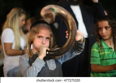 MERON,ISRAEL- September 2, 2016:  Orthodox Jewish boy blowing the shofar of Rosh Hashanah (ram's horn).  the Jewish High Holidays in Rosh Hashanah and Yom Kippur