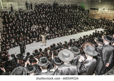 "Meron,Israel,February 25 2017-Rabbi Elimelech Biderman,Rabbi to his Jewish flock of religious Hasidim,during the grand ""tisch"" with his followers. ""tisch"" is a  tradition between Rebbe and his Hasidim"