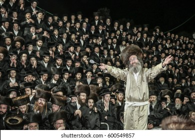 """Meron,Israel,February 25 2017-Rabbi Elimelech Biderman,Rabbi to his Jewish flock of religious Hasidim,during the grand """"tisch"""" with his followers. """"tisch"""" is a  tradition between Rebbe and his Hasidim"""