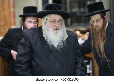 "meron,Israel-November 9,2016- Jewish Grand Rabbi of Shomer Emunim dynasty teaches Torah lessons to a group of Hasidic followers during the traditional Hasidic ""tisch"" gathering around table"