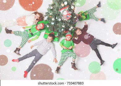 Merry Christmas 2017. Happy children celebrating Christmas lying near Cristmas tree. Kids dressed in elf costumes. A round dance, children's party Masquerade xmas. Aerial view