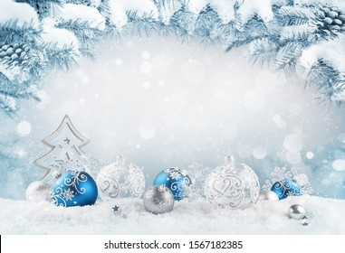 Merry Christmas background. Blue christmas balls and baubles and wooden decorative tree on the snow with fir branches. Mixed media.