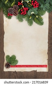 Merry christmas background border with fir, red berry sprays, mistletoe and pine cones over old parchment paper and oak wood.