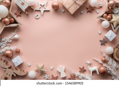 Merry Christmas background concept, winter holidays and happy new year card white gold wooden decorations frame border on pink pastel powdery table, flat lay, copy space, top close up view above