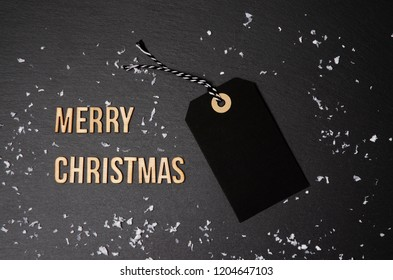 Merry Christmas background and price label.  Black Friday. Sales concept. Copy space.  Black paper label against a dark grey background. Black Friday shopping sale concept with Black ticket Sale tag