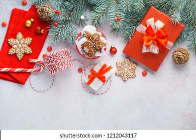 Merry Christmas background with traditional decoration. Red ribbons on gift boxes, cookies. Winter holidays concept. Copyspace, overhead shot.