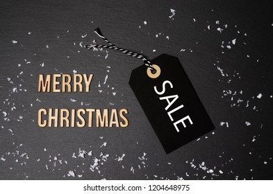 Merry Christmas black background and price label.  Black Friday. Sales concept. Copy space.  Paper label against a dark grey background. Black Friday shopping sale concept with ticket Sale tag