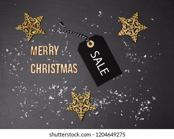 Merry Christmas black background and price label.  Black Friday. Sales concept. Copy space.  paper label against a dark grey background. Black Friday shopping sale concept with Black ticket Sale tag