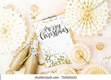Merry Christmas Card  and champagne with golden decorations. Flat lay, top view trendy holiday concept.