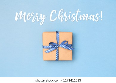 Merry Christmas card with gift box wrapped in kraft paper tied with blue ribbon in polka dots on blue background. Greeting card concept.