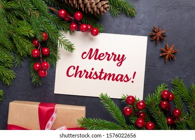 Merry Christmas card with paper, gift box, holly berries and fir tree branch on stone background. Top view - Image
