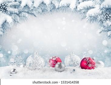 Frohe Weihnachtskarte. Rote Weihnachtsbälle und Bausteine auf dem Schnee mit Tannenästen.
