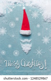 Merry Christmas card with Santa Claus symbol made with snow and Santa hat on blue background. Creative minimal holiday concept