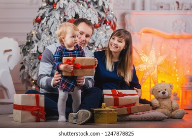 Merry Christmas celebration. Happy family mother father and baby at christmas tree with Xmas gifts at home.