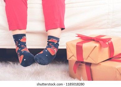 Merry Christmas child's feet next to christmas gifts