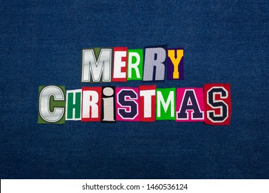 Merry Christmas colorful word text collage, multi colored fabric on blue denim, winter holiday, horizontal aspect