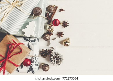 merry christmas concept. presents with ornaments pine cones anise and lights on rustic white wooden background top view, space for text. seasonal greetings card. happy holiday