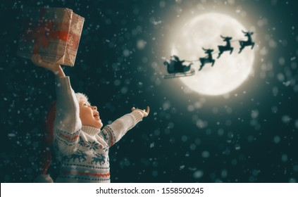 Merry Christmas! Cute little child with xmas present. Santa Claus flying in his sleigh against moon sky. Happy kid enjoy the holiday. Portrait of girl with gifts on dark background.