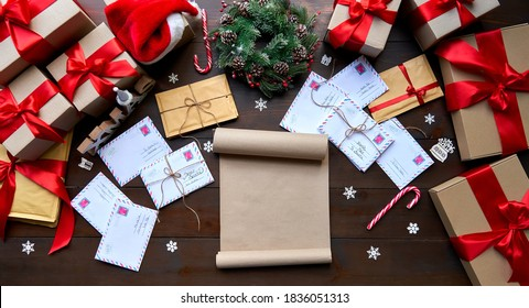 Merry Christmas decorated wooden table with wish list, post mail letters envelopes, gifts boxes, presents with red ribbons. Xmas Santa desk workplace background concept. Top view above, flat lay.