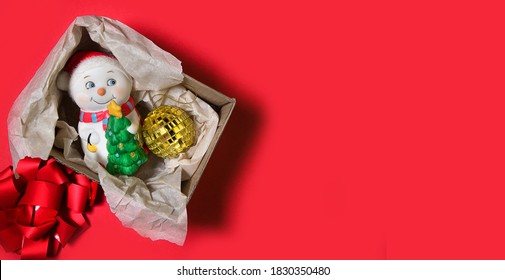 Merry christmas decoration with little snowman and golden ball in cartoon box. Red background. Top view. Copy space. Holiday wrapping.