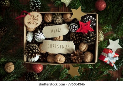 Merry Christmas decorative background. Banner, poster or greeting car template on Merry Xmas. Holiday ornate elements, golden and brown pine-cones, stars and walnuts in the box. Christmas gift concept