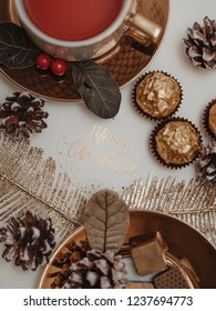 Merry christmas - Delicous christmas tea and truffles and golden wrapped chocolate treats served on golden plate decorated with berries, surrounded by candlelit stars and pine cones and gold ferns