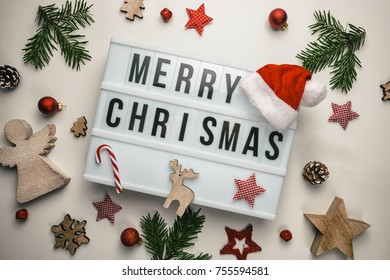 Merry Christmas displayed on a vintage lightbox with santa hat and decoration, concept image