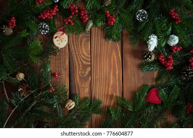 Merry Christmas fir frame on dark wooden background. Banner, poster or greeting car template on Merry Xmas. Copy space in the middle.