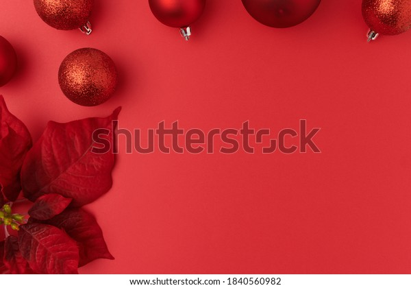 Merry Christmas. flat lay with poinsettia and Christmas balls on red background.