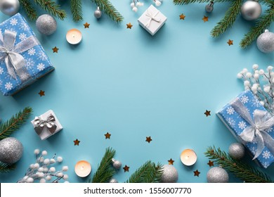 Merry Christmas gift boxes with silver ribbon bow on blue festive background decorated balls candles tree, happy 2021 new year winter handmade holiday present concept, flat lay, copy space top view