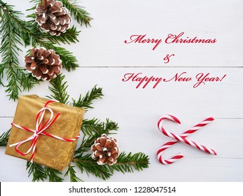 Merry Christmas greeting card with candy cane, gift, cones and fir branches over white wooden background.