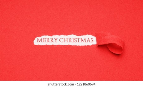 merry christmas greeting seen through hole peeled in red paper background
