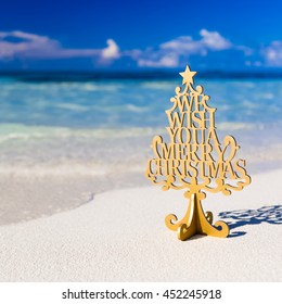 Merry Christmas. Christmas greeting statue with rustic wood and ornaments. Xmas beach background.