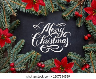 Merry Christmas hand lettering inscription with golden balls, tree branches and cones on a wooden background. Christmas greeting card.