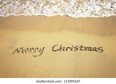 Merry Christmas handwritten in sand on beach