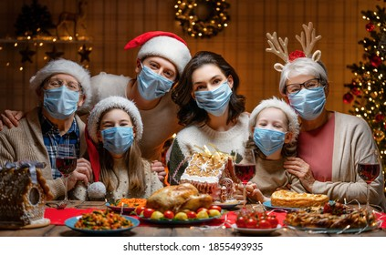 Merry Christmas! Happy family are having dinner at home. Celebration holiday and togetherness near tree. People are wearing facemasks. - Shutterstock ID 1855493935