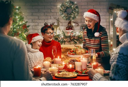 Merry Christmas! Happy family are having dinner at home. Celebration holiday and togetherness near tree. - Shutterstock ID 763287907