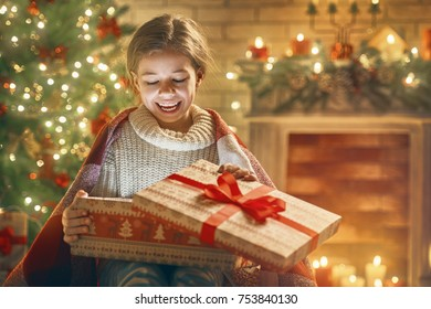 Merry Christmas and Happy Holiday! Cute little child girl with present gift box near tree at home.