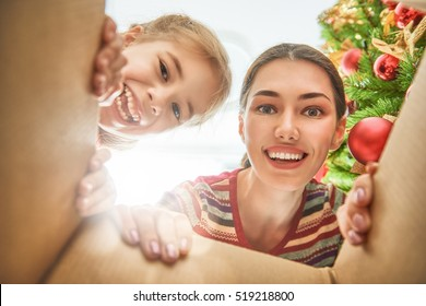 Merry Christmas and Happy Holidays! Cheerful mom and her cute daughter girl opening a Christmas present. Parent and little child having fun near Christmas tree indoors. View from inside of the box.