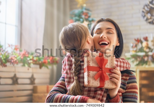 聖降誕祭お目出とう!元気なお母さんとかわいい娘が贈り物を交換して。家の中の木の近くで楽しむ親子。部屋の中の贈り物で家族を愛して。