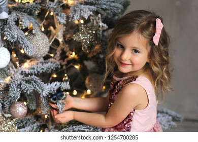 Merry Christmas and Happy Holidays. Cute little child girl is decorating the Christmas tree indoors. The morning before Xmas. Portrait kid close up. Winter holiday concept. New year 2019 .