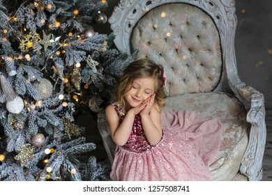 Merry Christmas and Happy Holidays. Cute little girl smiling and dreaming about christmas miracles on the background of the Christmas tree. Portrait kid close up. New year 2019 .