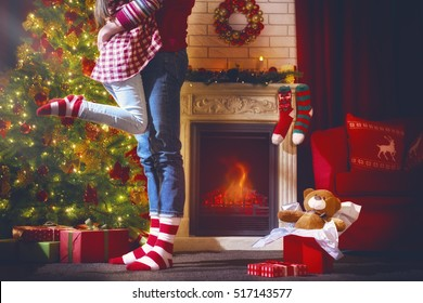Merry Christmas and Happy Holidays! Cute child hugs a parent and rejoice in the gift. Christmas family traditions.