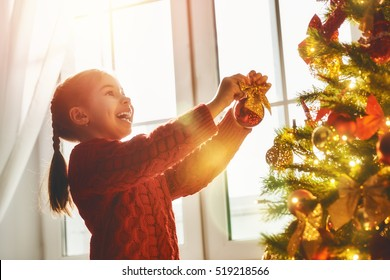 Merry Christmas and Happy Holidays! Cute little child girl is decorating the Christmas tree indoors. The morning before Xmas. Portrait kid close up.